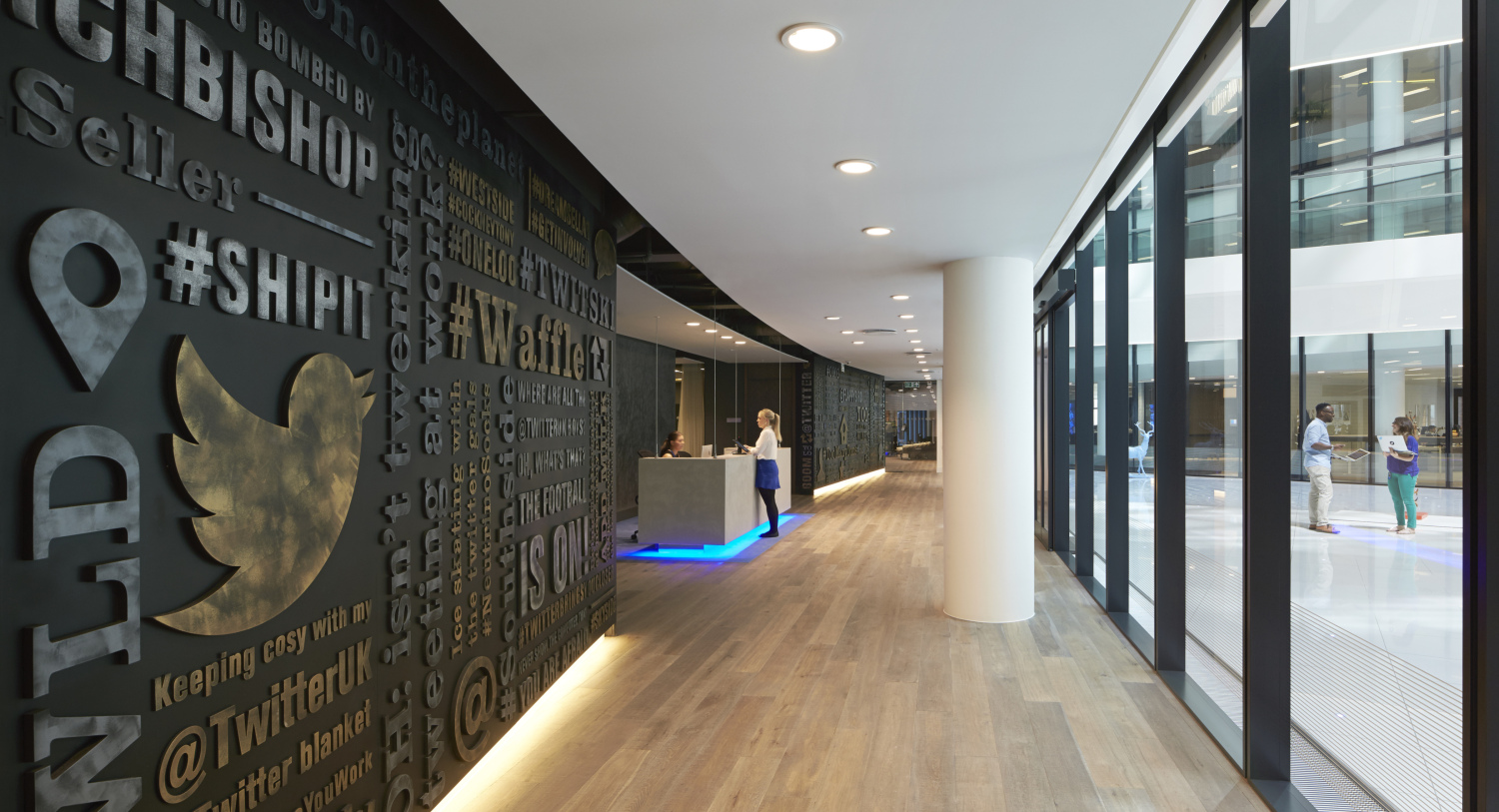 Wall with Twitter bird logo, reception desk beyond.